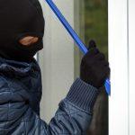 burglar forcing a window with crowbar